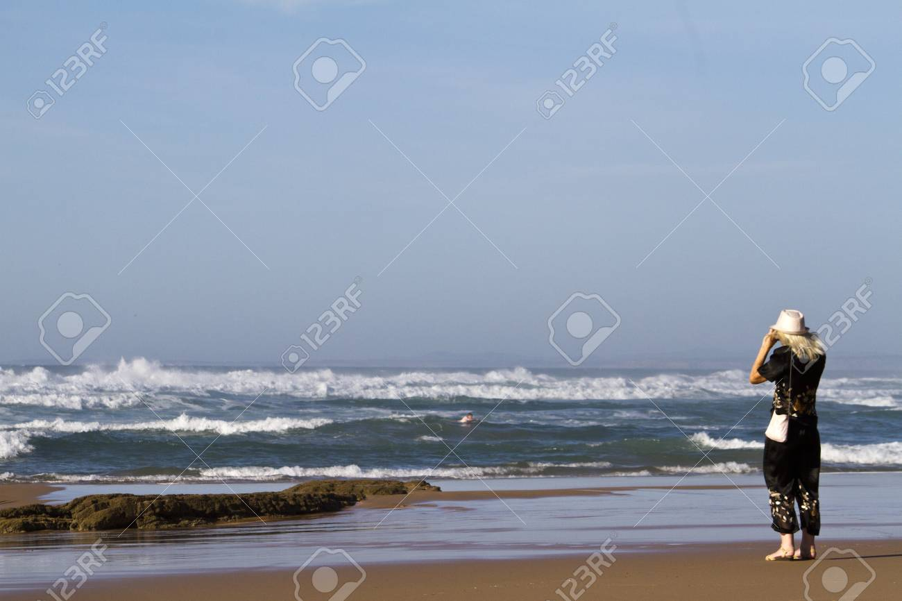 View of a woman admiring the endless sea in Sagres nearby region on the Algarve, Portugal. Stock Photo - 12210244