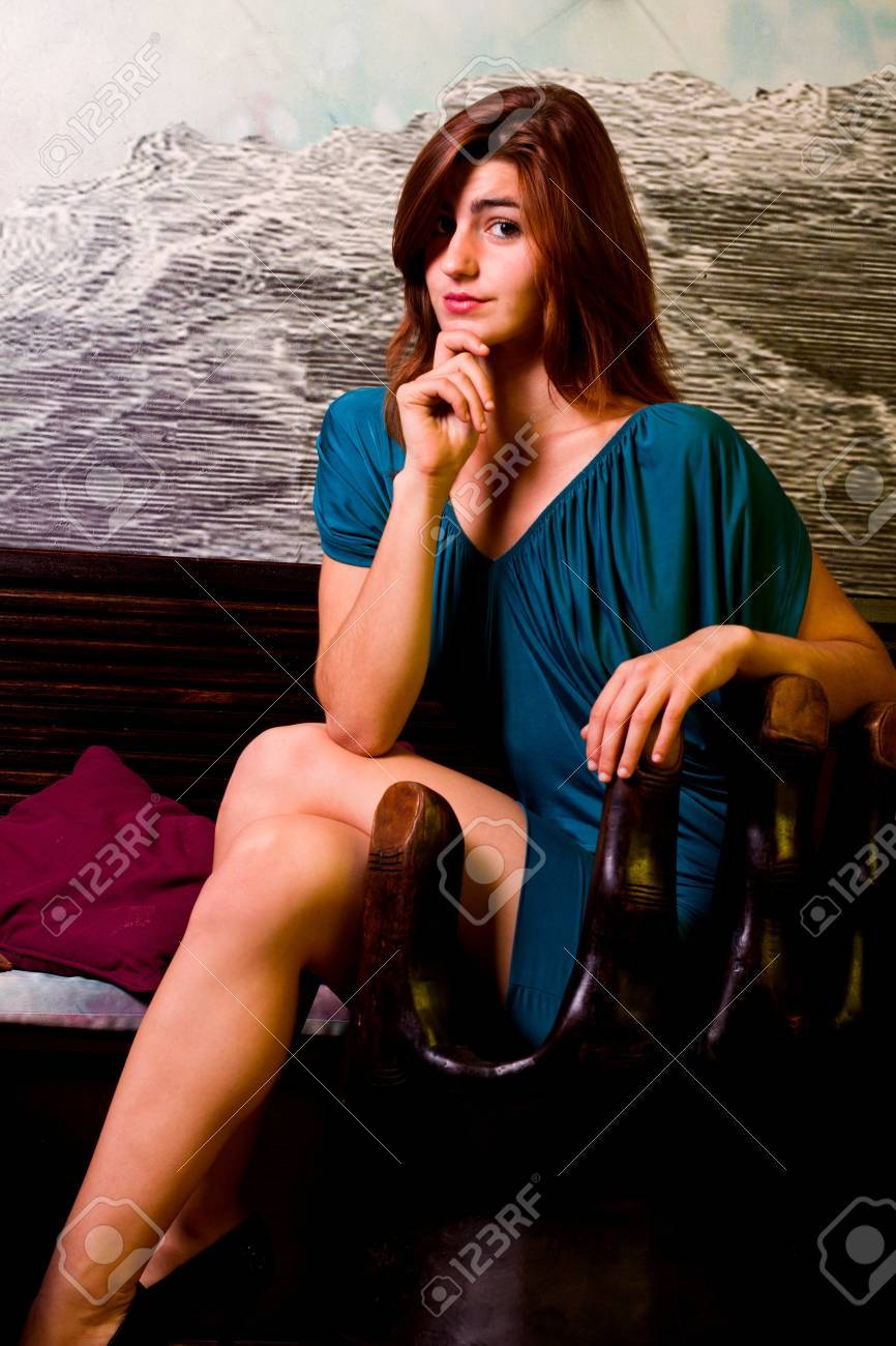 View of a beautiful young girl on a blue dress inside a bar pub. Stock Photo - 12212121