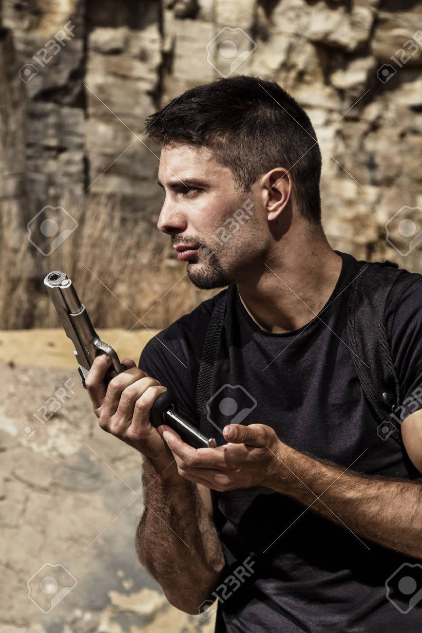 View of a menacing man reloading a handgun in a black shirt and dark shades on a stone quarry. Stock Photo - 17497680