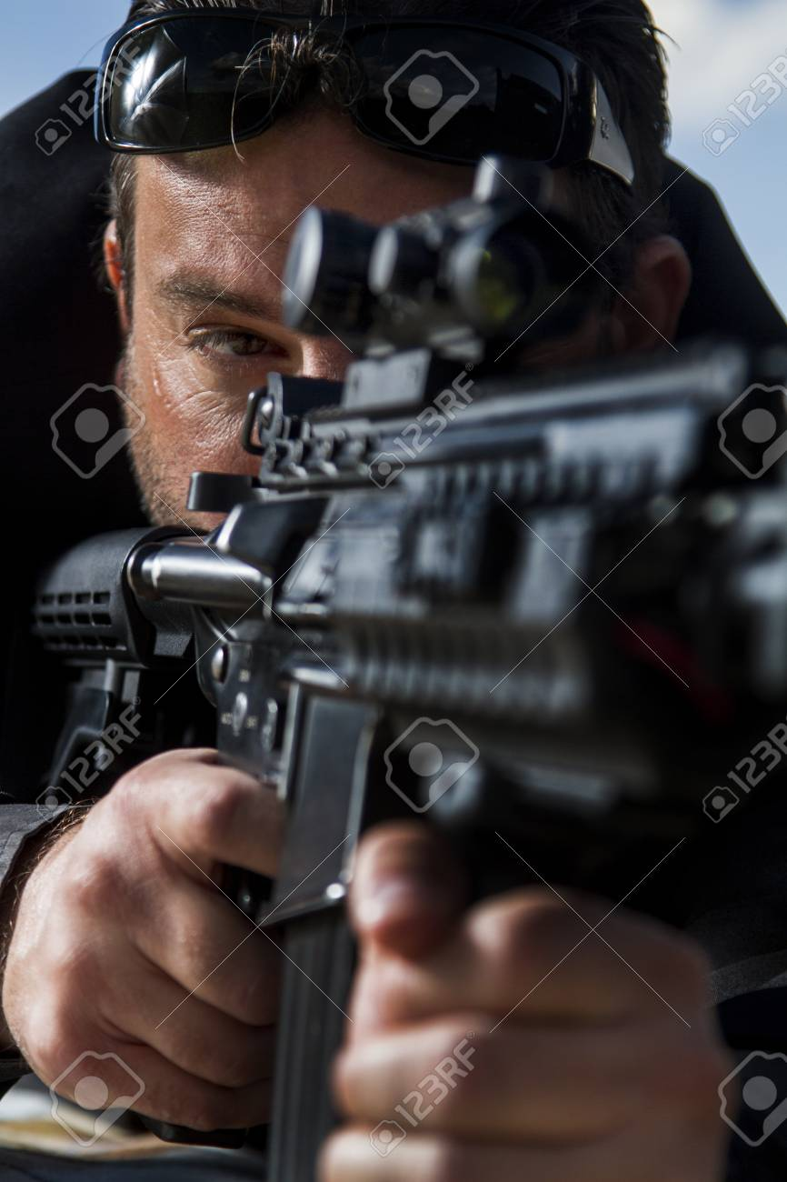 View of a contracted type killer agent wandering with a long jacket and machine gun. Stock Photo - 17496467