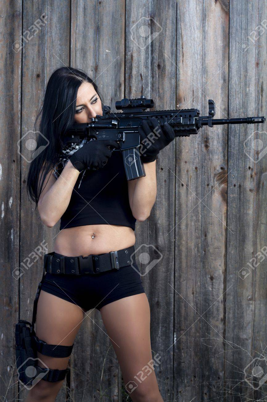 View of a beautiful action girl holding a weapon in a outdoor location. Stock Photo - 17489366