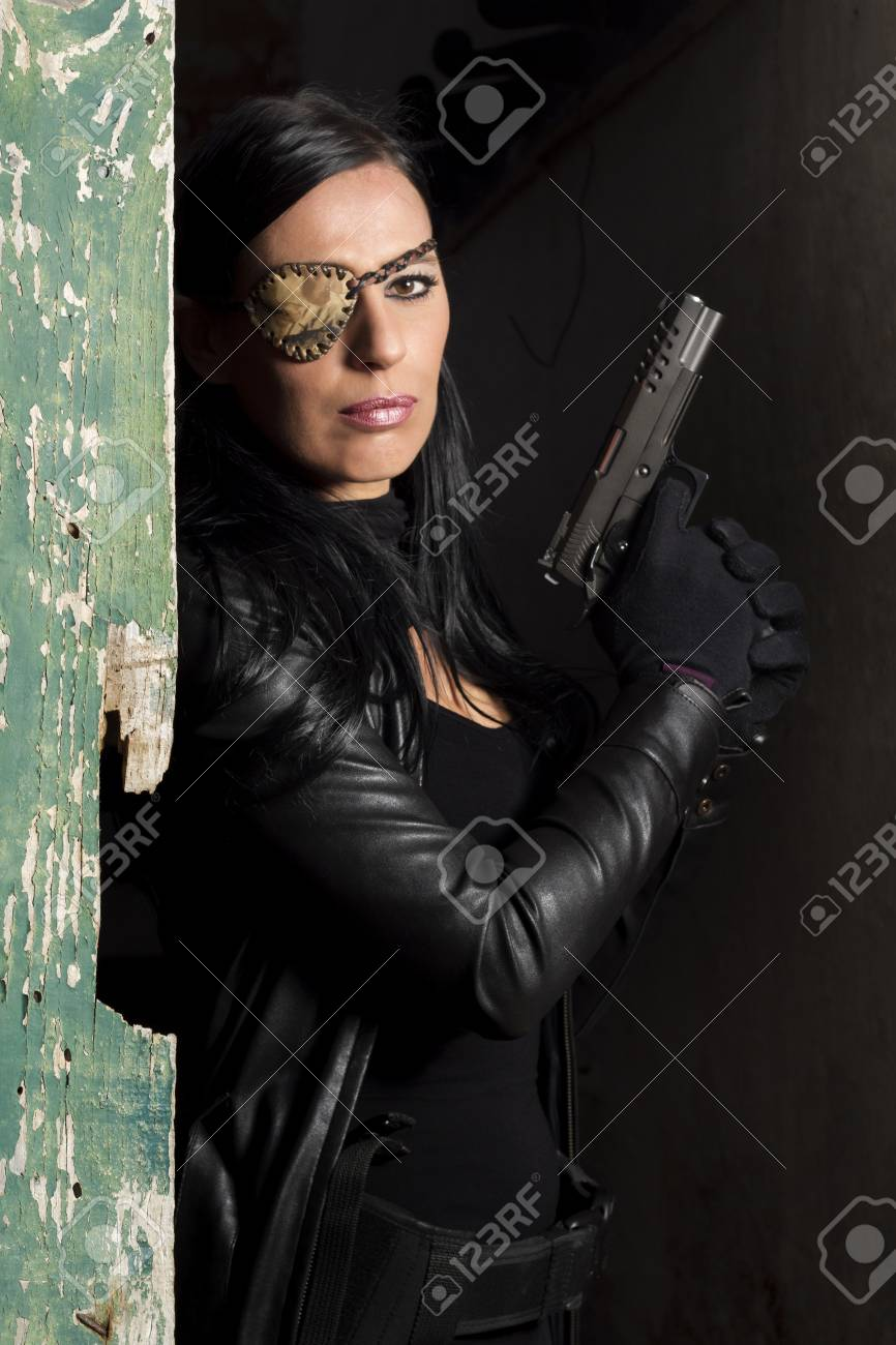 View of a beautiful action girl holding a weapon in a outdoor location. Stock Photo - 17489285
