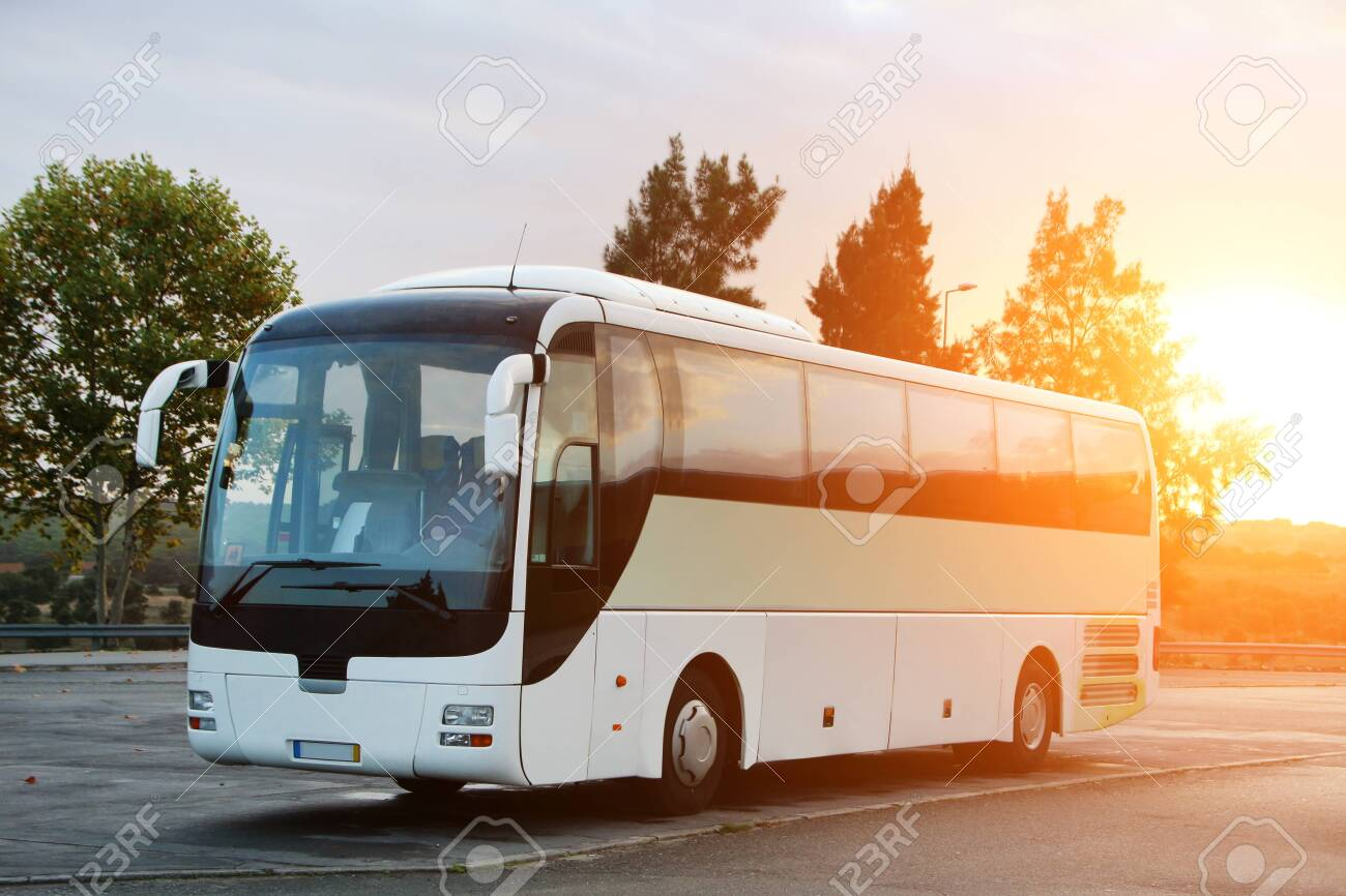 Passenger Bus parked on the road at sunrise. - 125406134