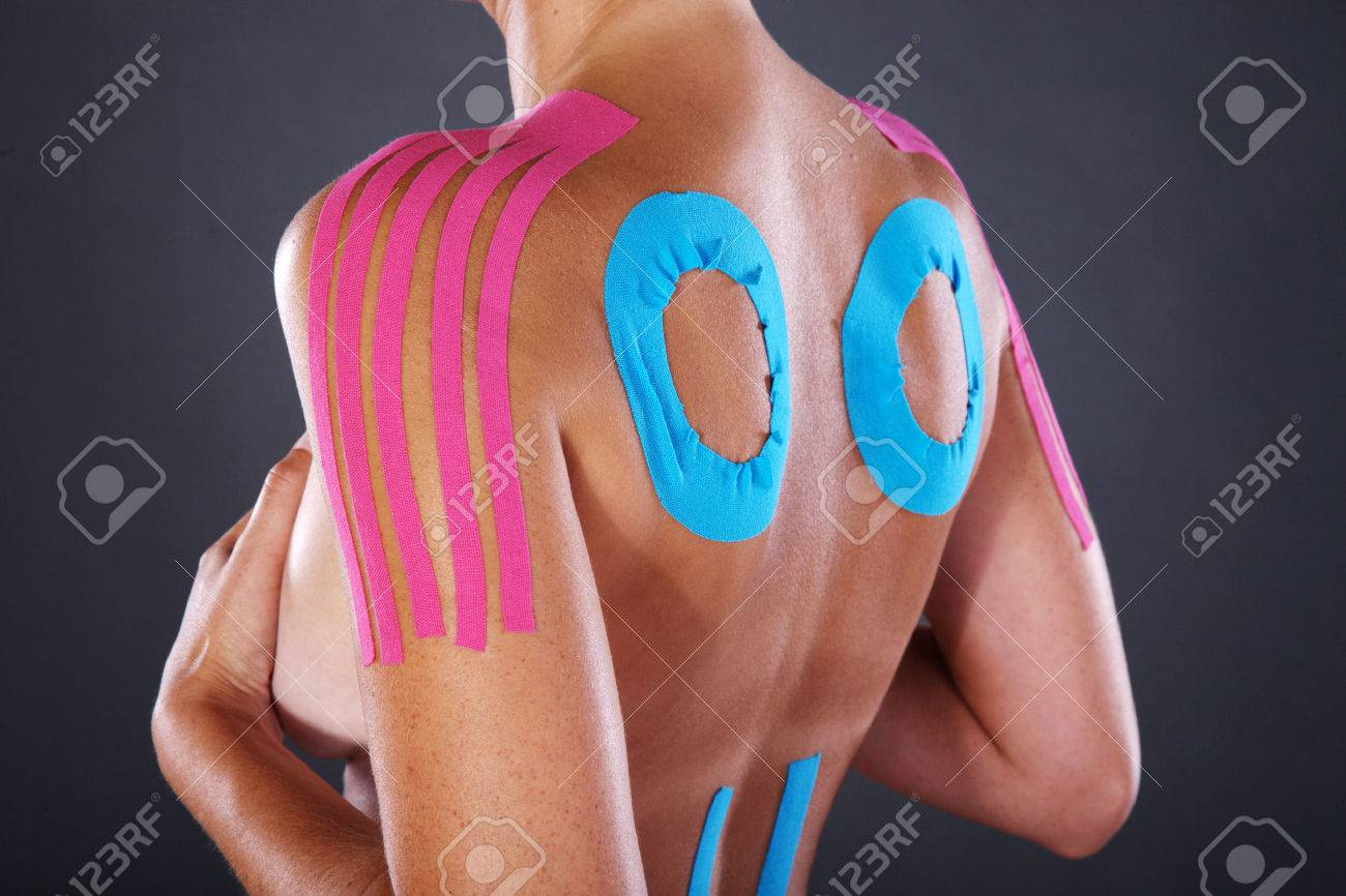 young pretty woman with sports taping on back and shoulder - 28588768