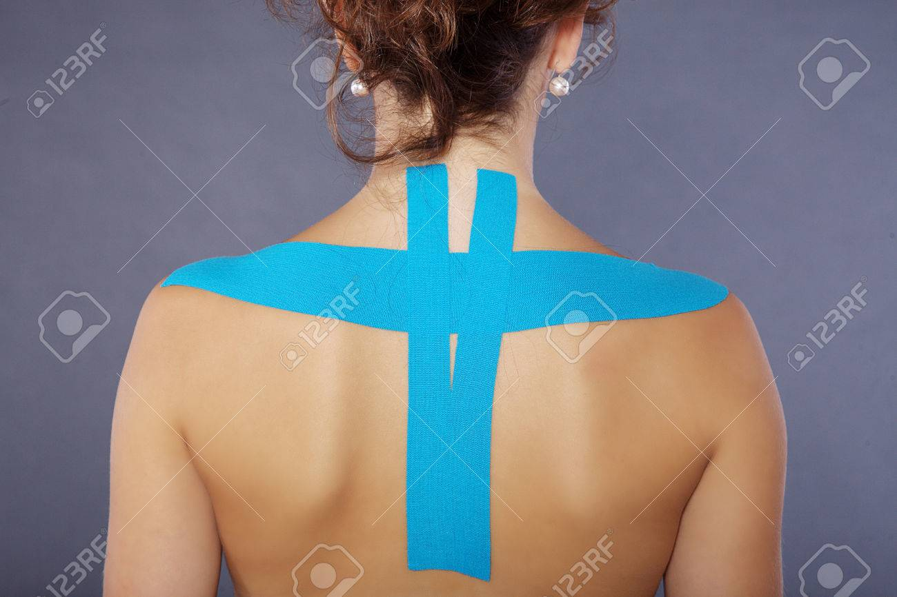 young pretty woman with sports taping on neck and shoulder - 28589841