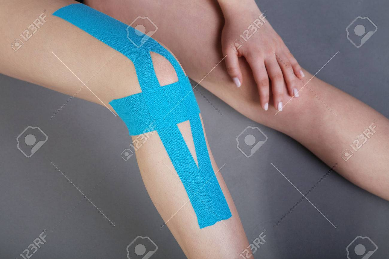 young pretty woman with sports taping on knee Standard-Bild - 28590060