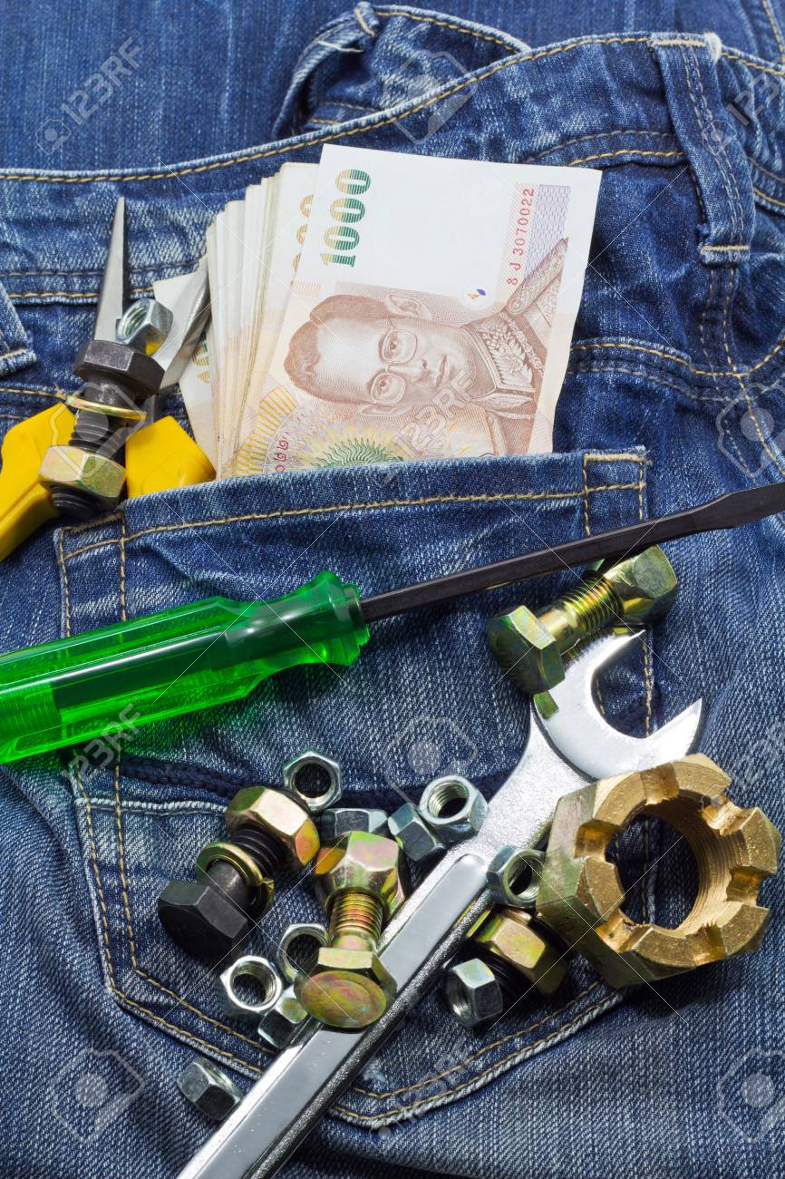 tools and cash on a denim workers pocket Stock Photo - 15221396