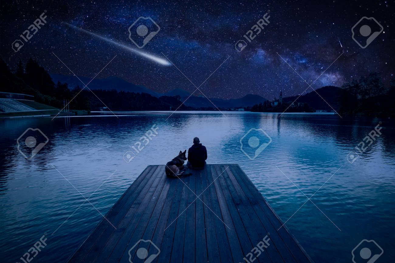 Man with dog looking at Perseid Meteor Shower at lake Bled - 106234891