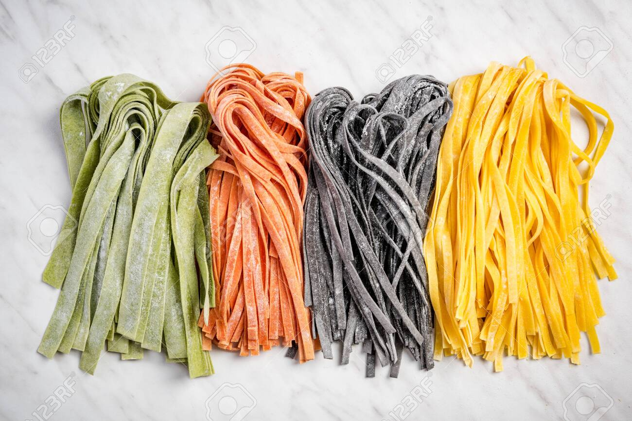 Variety of fresh raw homemade pasta. White marble background. - 122026048