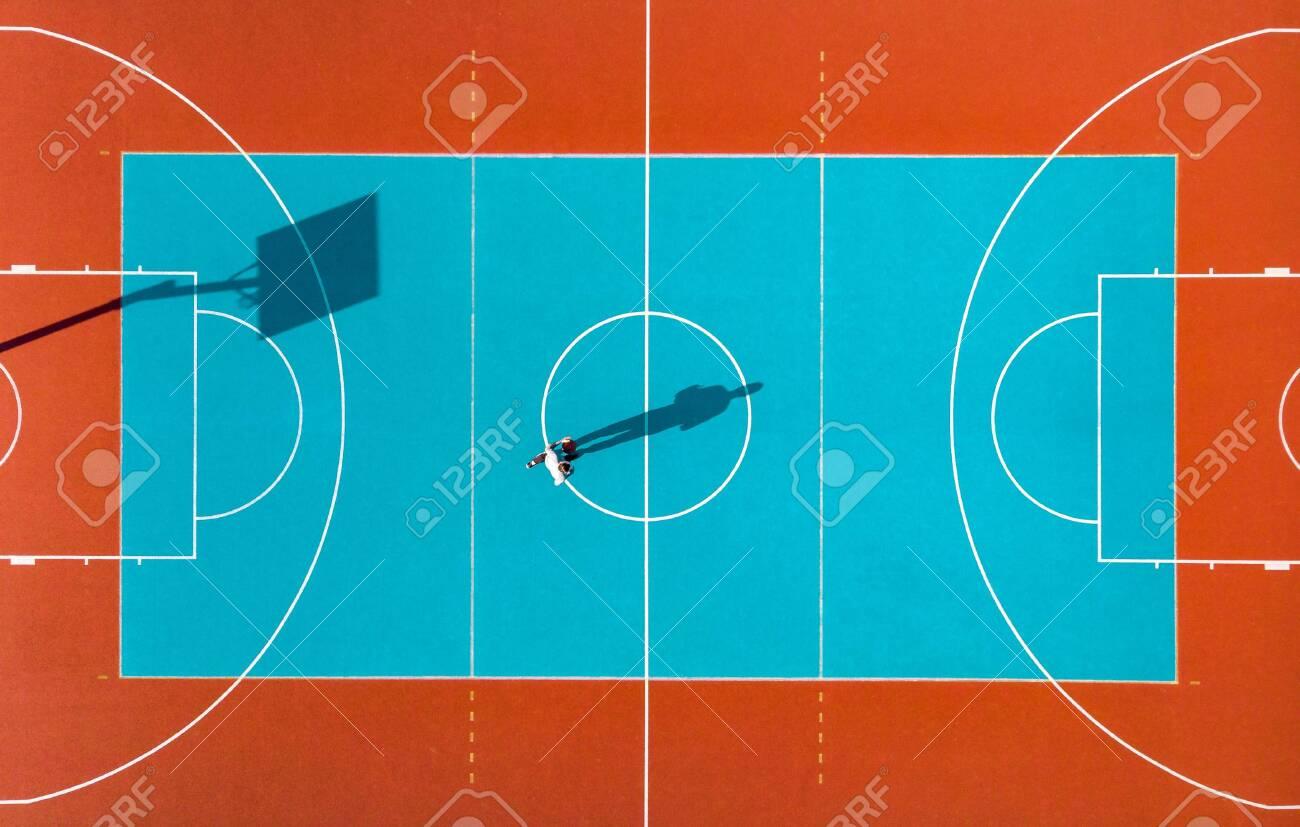 Basketball Player, Long Shadows on Basketball Court, Creative Visual Art, Aerial Image. - 124517996