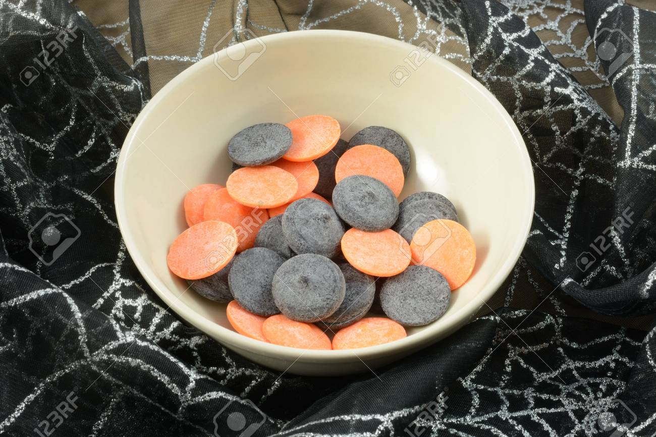 Orange and black colored white chocolate candy discs meltable..
