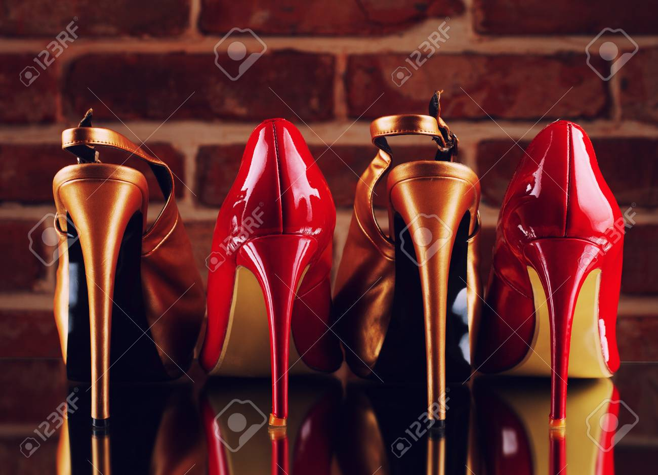 cf62cdf71ec Red and gold high heels on the red brick wall background