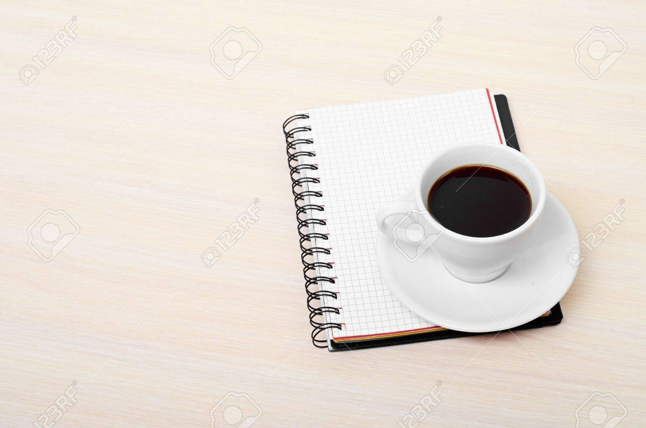 Coffee cup with note book on table Stock Photo - 14673322