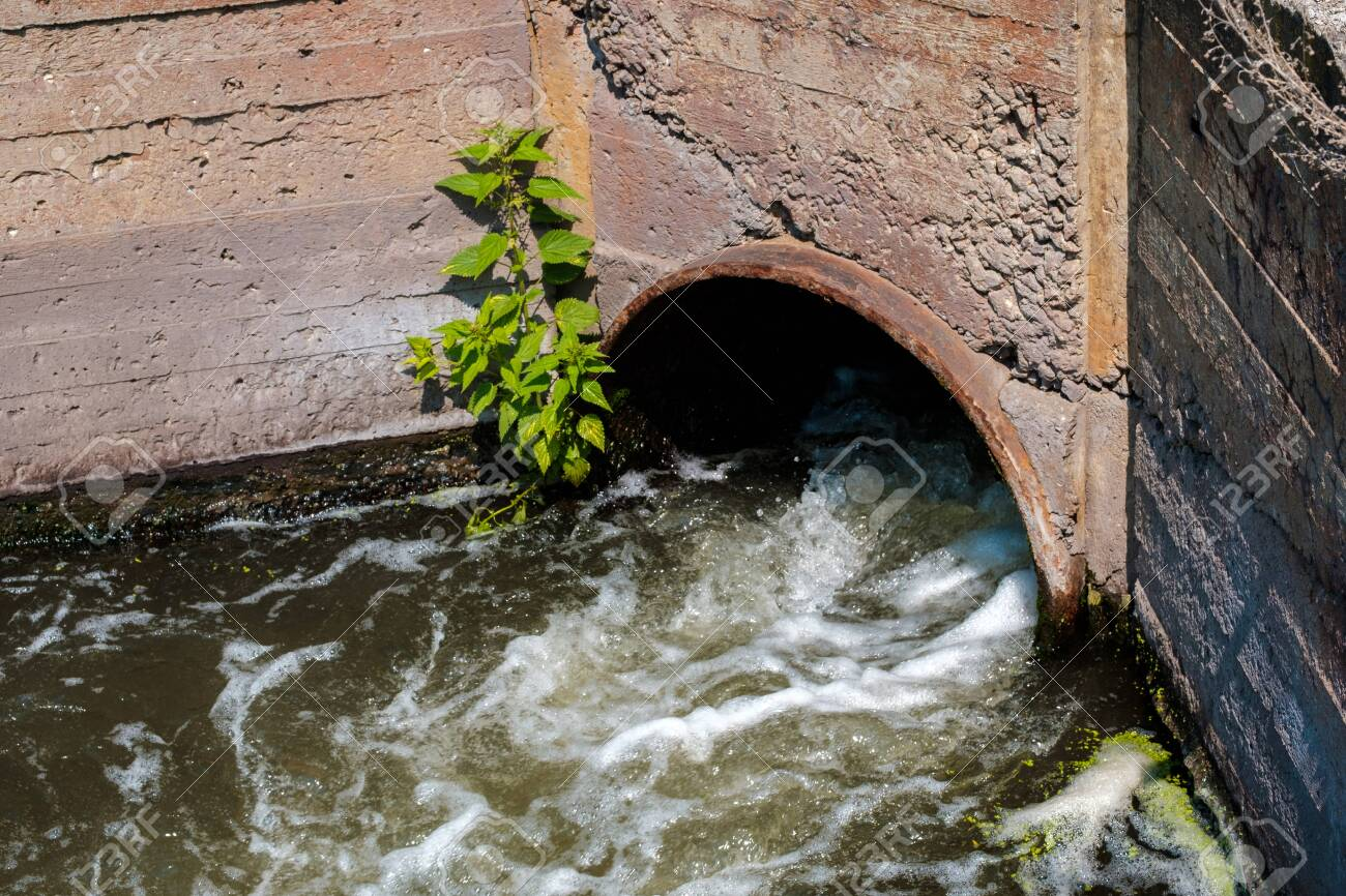 a stream of water flowing out of a pipe in a concrete wall. current and turbulence - 147200162