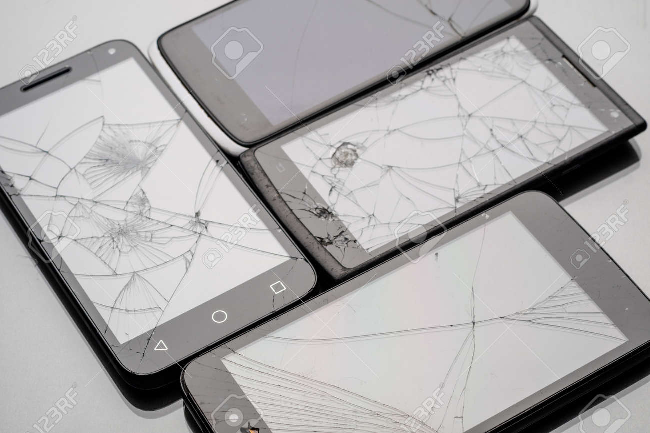 Four badly broken smartphones with glare-free lighting. cracked glass on four phones - 149477399