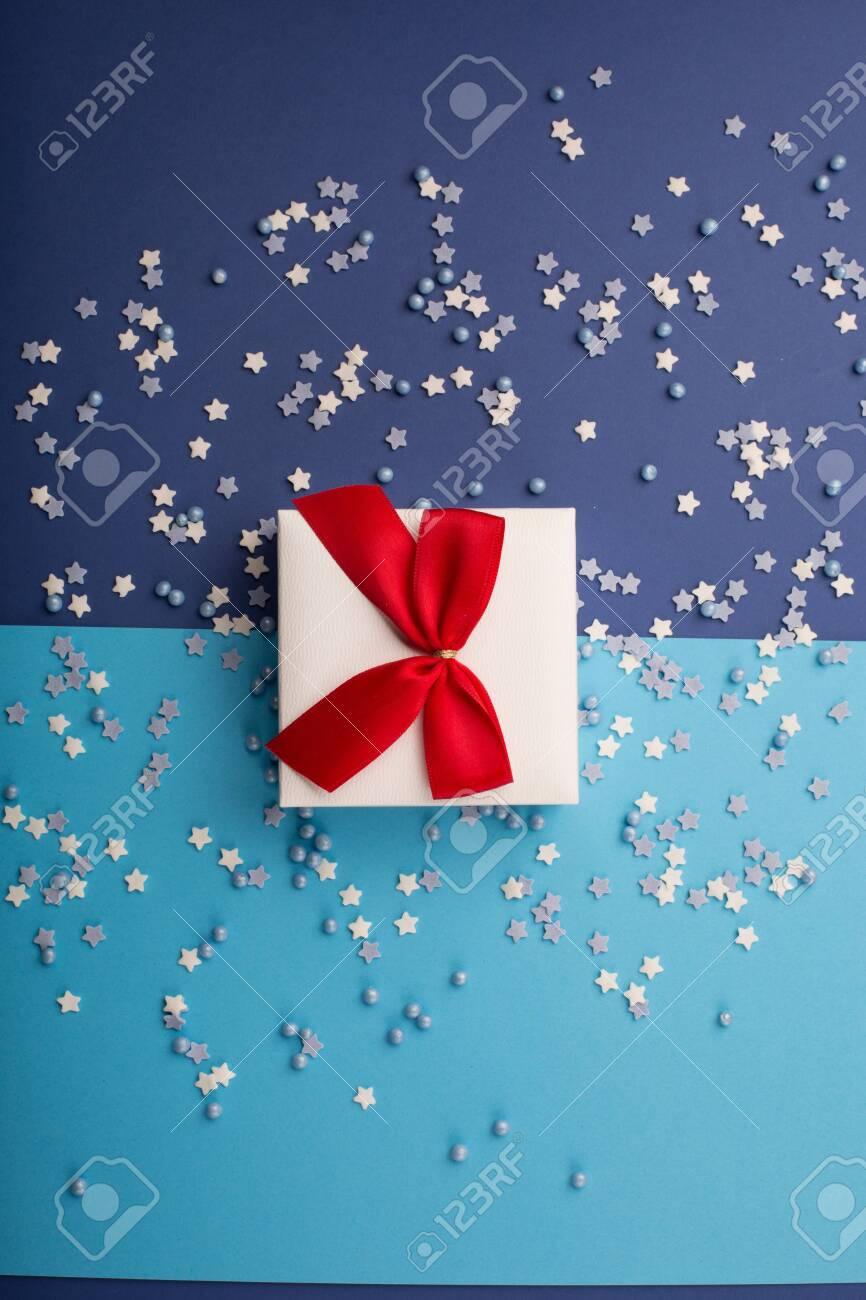 Happy Valentine's Day card with gift, small stars and white gift with red bow on classic blue background. Holiday time concept. Mockup template. Top view - 137251104