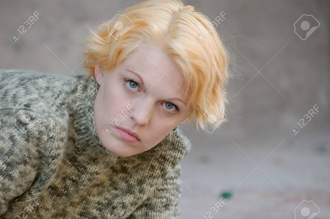 Blonde woman in a green sweater posing outdoors Stock Photo - 9330839