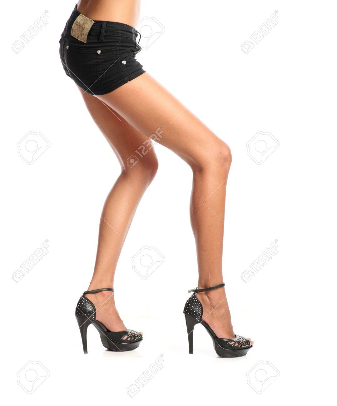 A young pretty girl standing in black jeans shorts and boots in the Stock Photo - 13392991
