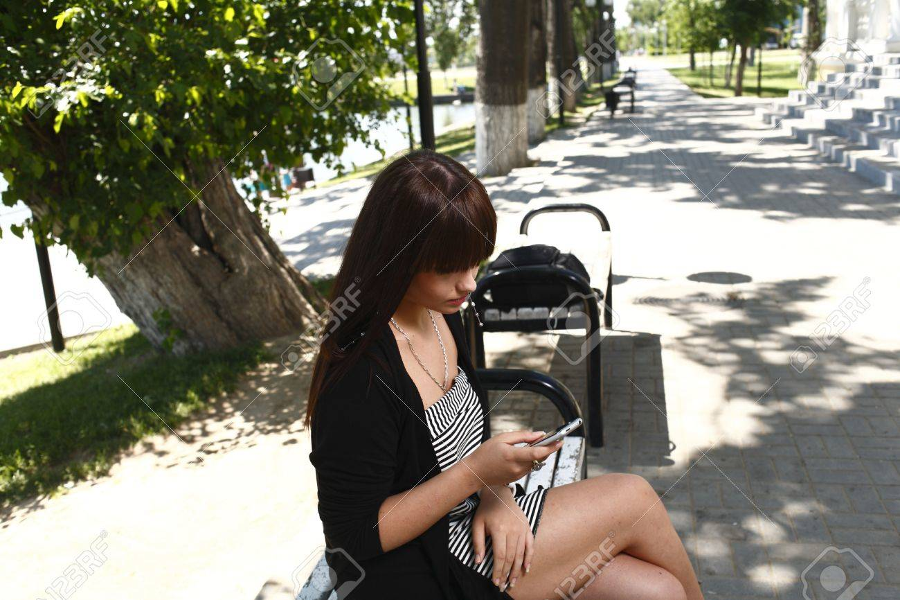 Calling by  phone - Beautiful brunette girl outdoors in summer Stock Photo - 13393331