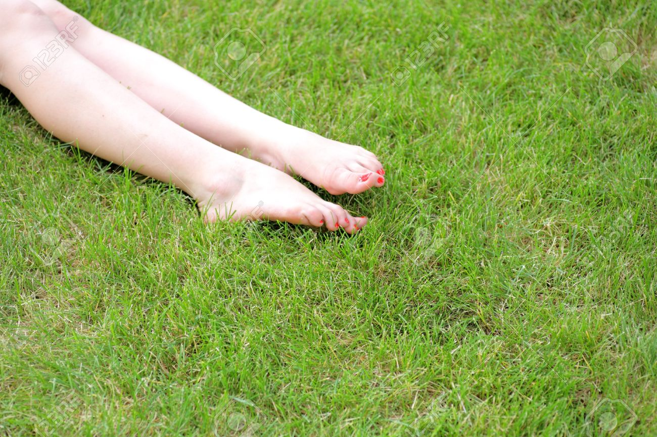 Perfect Feet In The Sun With Shaved Legs On A Meadow Of A Young Sexy Woman
