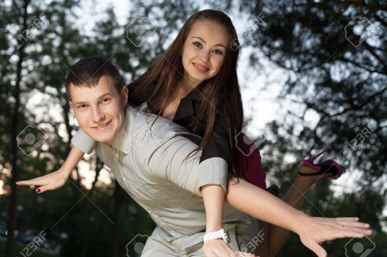 Young loving couple piggybacking in the park in the sunset closeup Stock Photo - 19505049