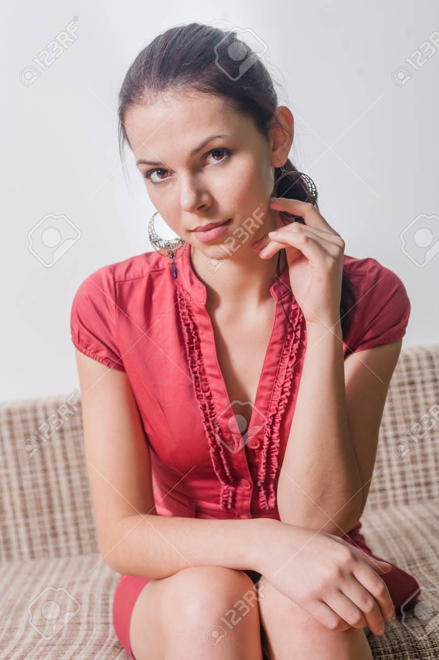 brunette looking at camera  20s female weared red dress sitting on sofa indoors Stock Photo - 23728890