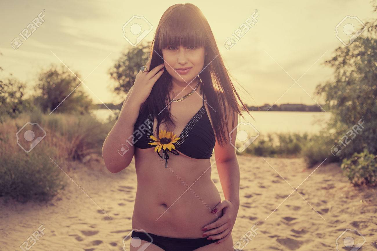women on beach with sunflower in her breasts stock photo, picture