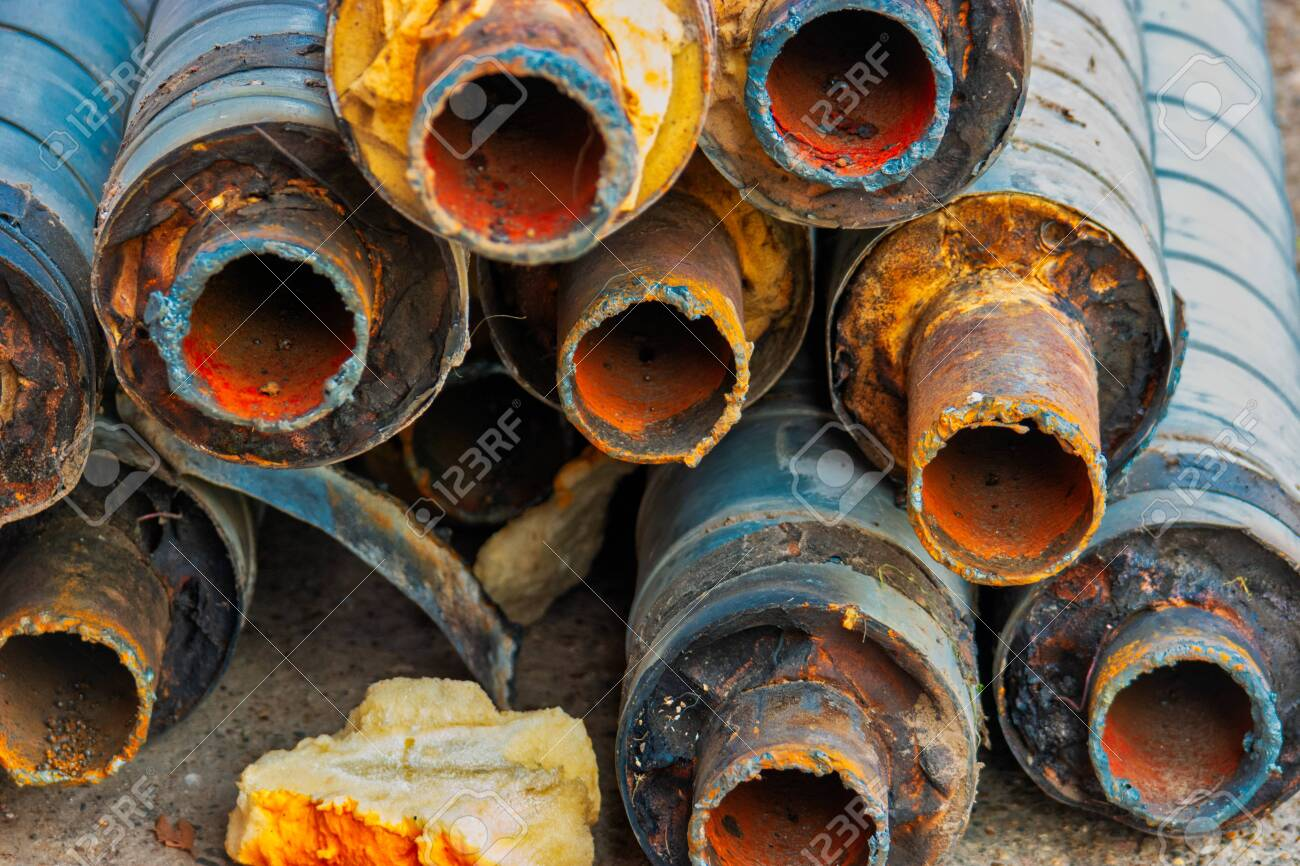 Water Pipeline repair. Large rusty steel pipe with insulation on the construction site in a plastic tube wrapper lying on the yard in a bunch horizontally. Rusty old pipeline stacked up - 122837477