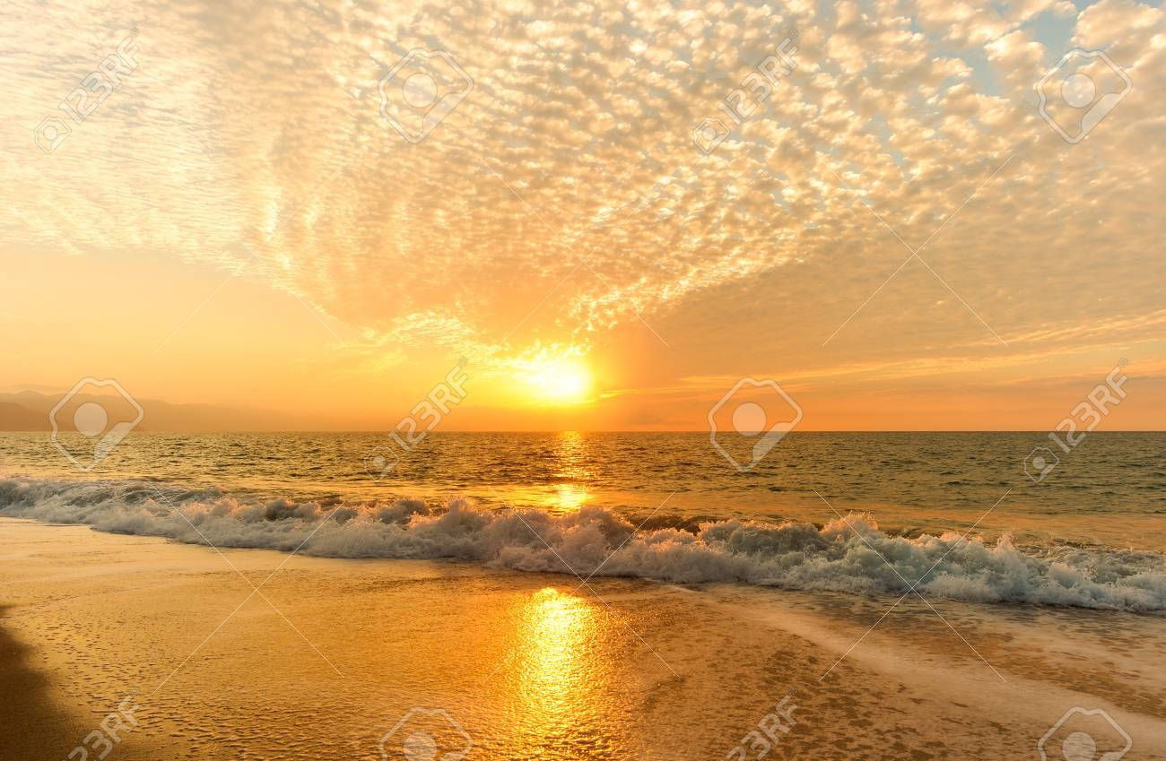 Ocean Sunset Is A Golden Reflection Off A Gentle Wave Rolling