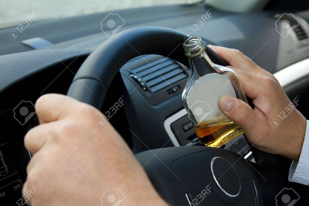 Driver with a bottle of alcohol sits behind the steering wheel Stock Photo - 10352201