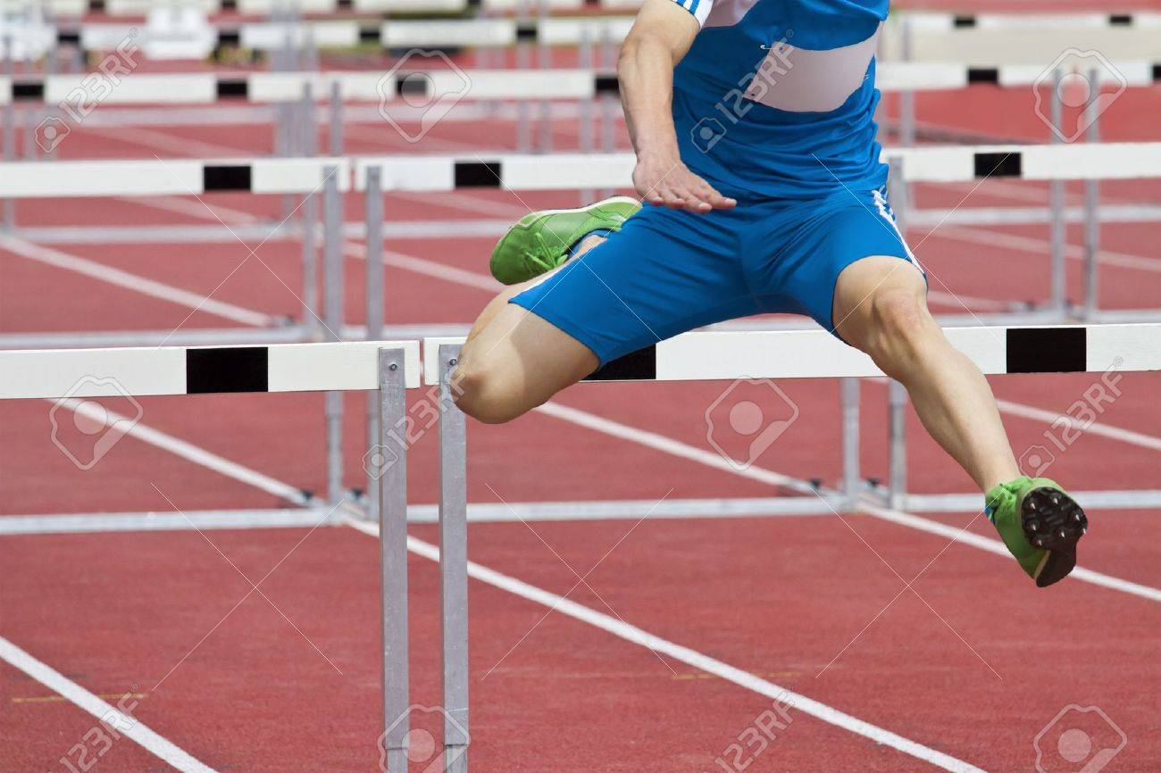 hurdle runner leaping over the hurdles - 14598911