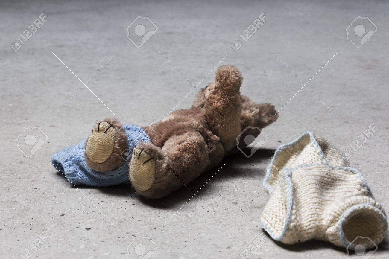 Stripped teddy with raised arm on concrete floor Stock Photo - 17772385