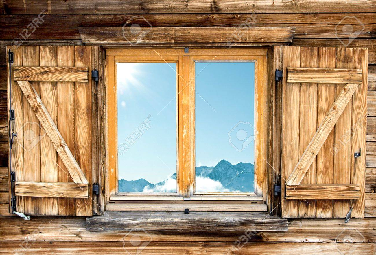 Weathered facade of a mountain hut with mountain reflection in the window - 18982093