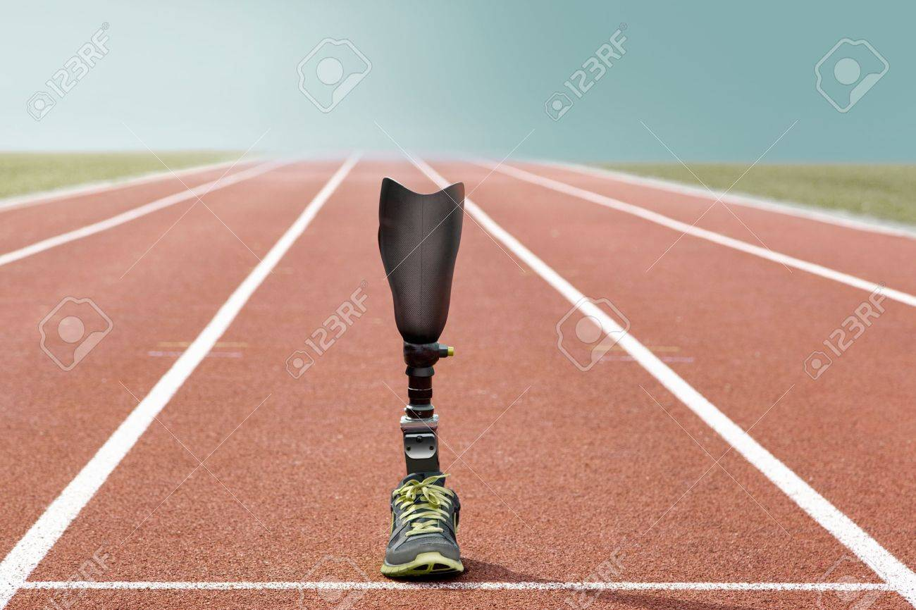Athletic sports prosthesis of a disabled athlete stands on a tartan track - 19577098