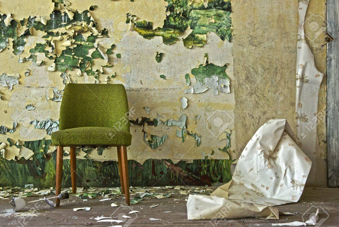 Old chair stands in front of a flaked off wall - 20987539