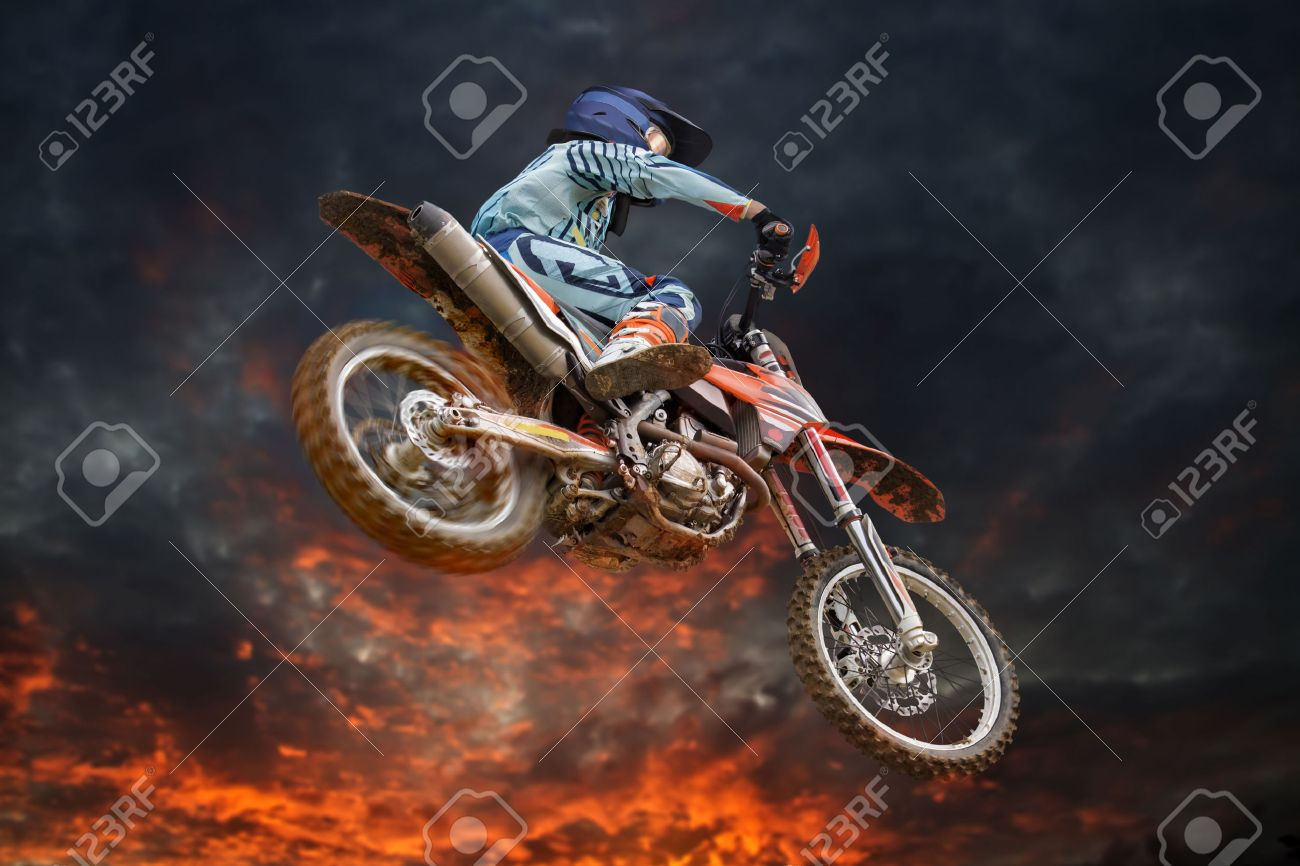 Jumping motocross rider with firestorm in the background and red glowing spinning rear wheel - 30210333