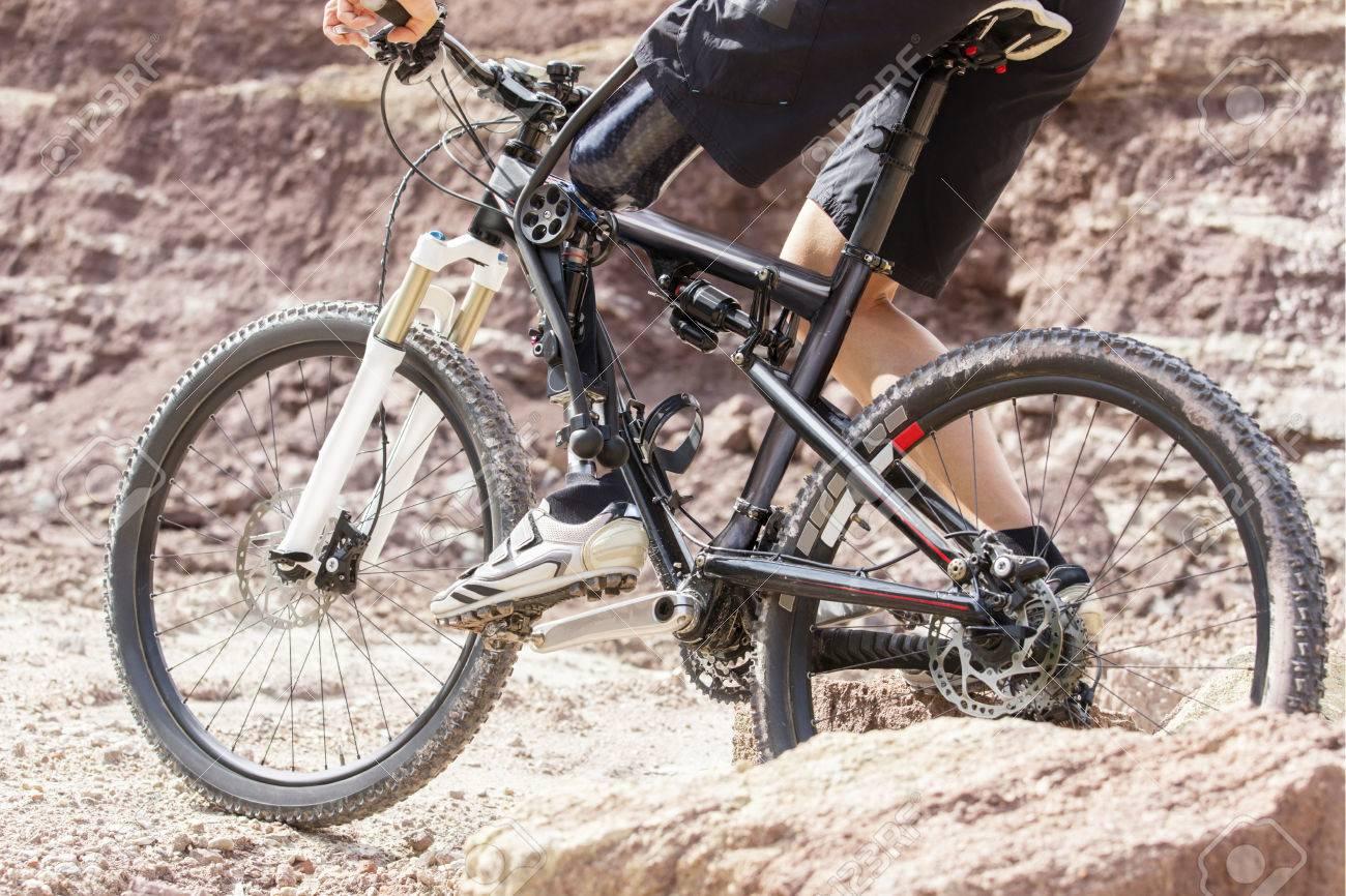 Shot of mountain bike rider with leg prosthesis between rocks. - 31280181