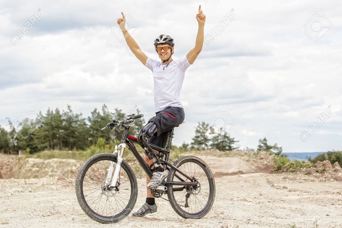 Shot of young mountain bike rider with leg prosthesis raising up his arms - 31280184