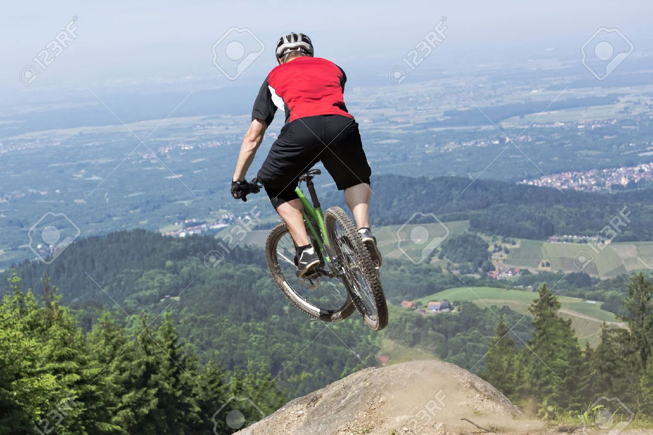Vue Arrière Du Coureur De Vélo De Montagne Qui Saute Par-dessus Un Kicker  De Chemin De Terre. Le Point De Vue Choisi Donne L'impression D'un Saut  Dans Le ...