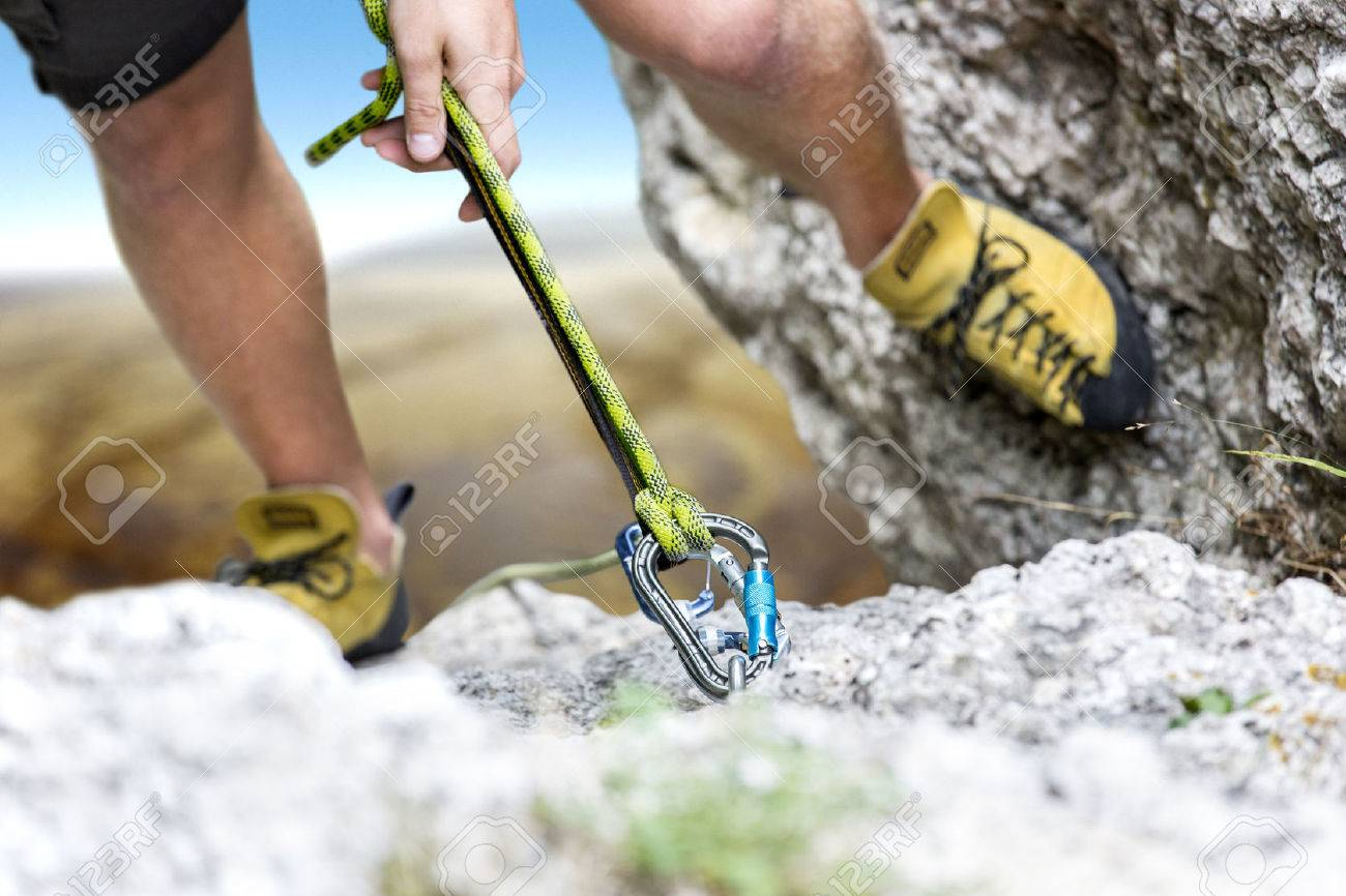 Climber reaches the summit of a mountain. Focus is on the rope and the carabiner - 44764817