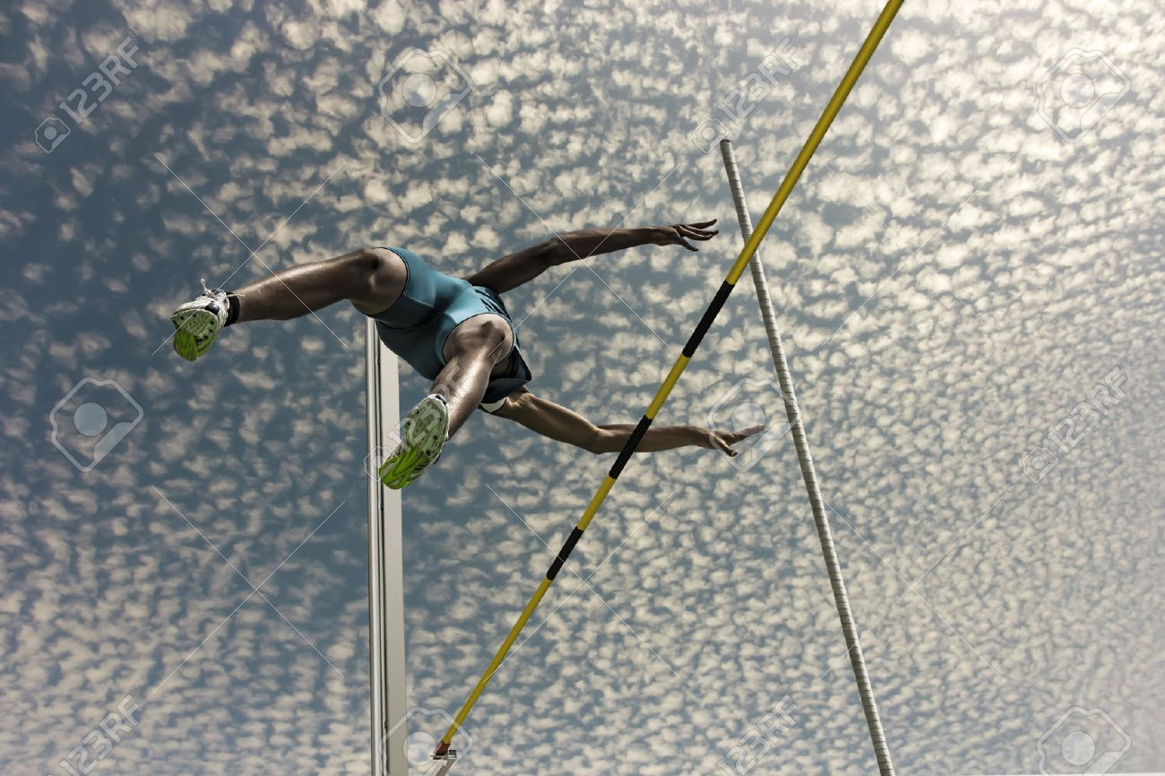 Male pole vaulter jumps over the yellow black striped bar - 54943263