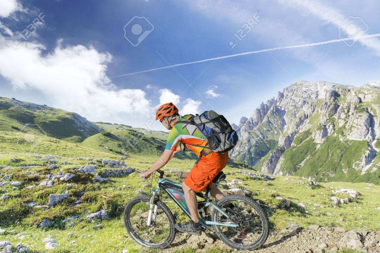 E bike traveler with backpack rides a mountain trail - 56543875