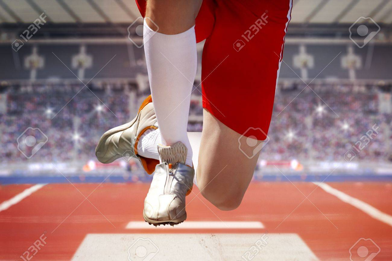 Long jumper in a stadium jumps into the sand box. The background shows fully occupied spectator terraces with sparkling flashlights. - 57552428