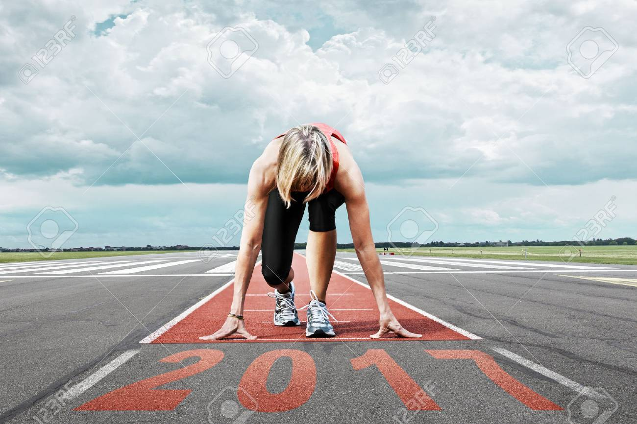 Female runner waits for the 2017 start on an airport runway. In the foreground perspective view of the date 2017. - 63566614