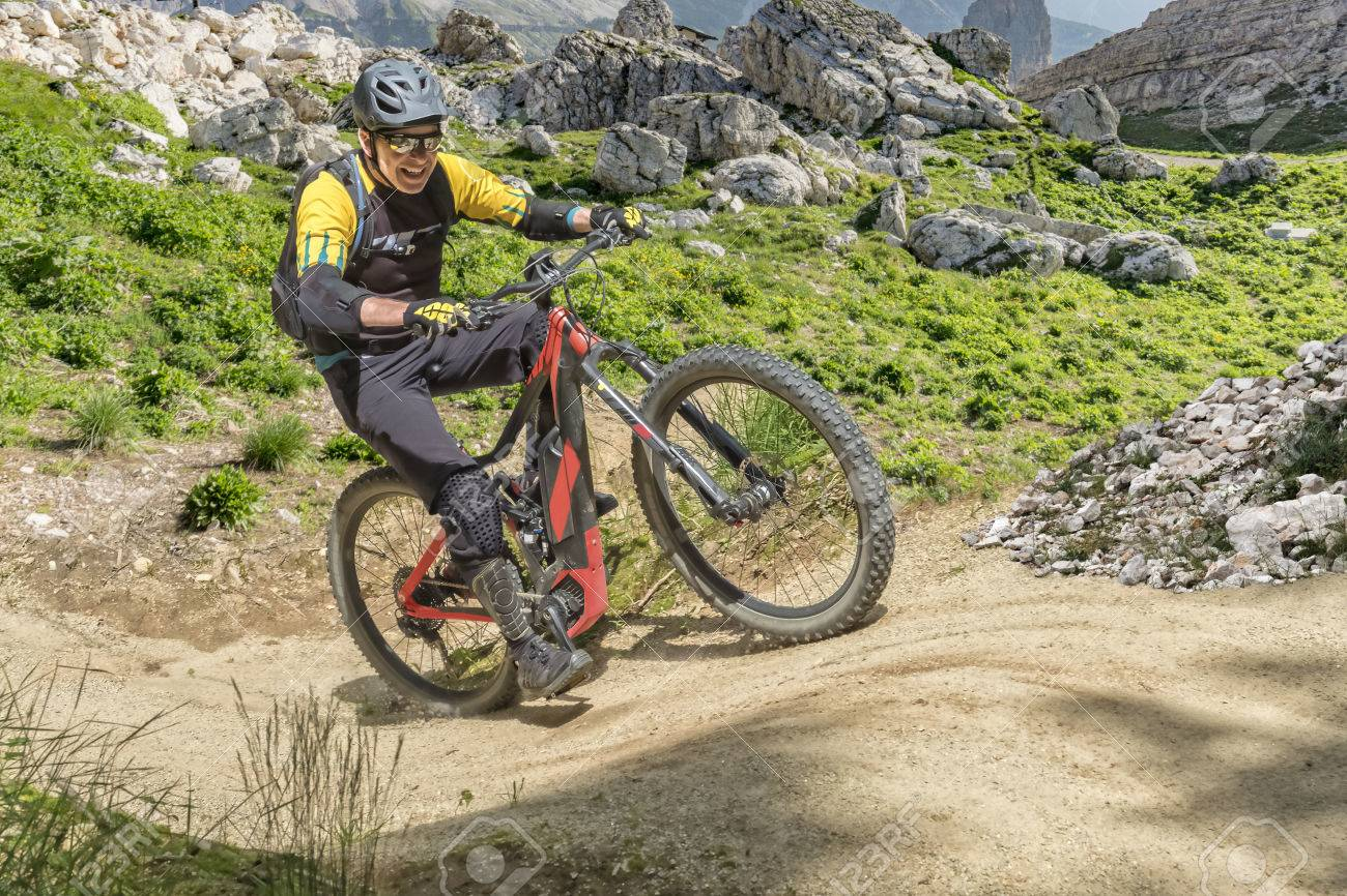 E bike rider in middle age enjoys the power of the e bike on a steep uphill trail. - 81560560