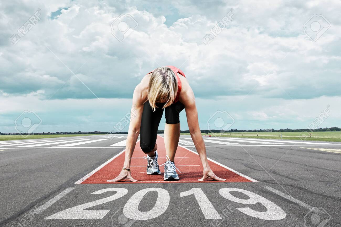 Female runner waits for her start at an airport runway. In the foreground the painted date 2019 symbolises the year. - 121633062