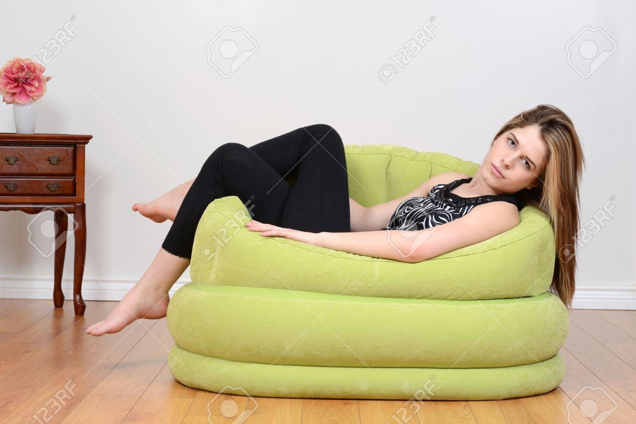 Teen Relaxing In Green Bean Bag Chair Stock Photo