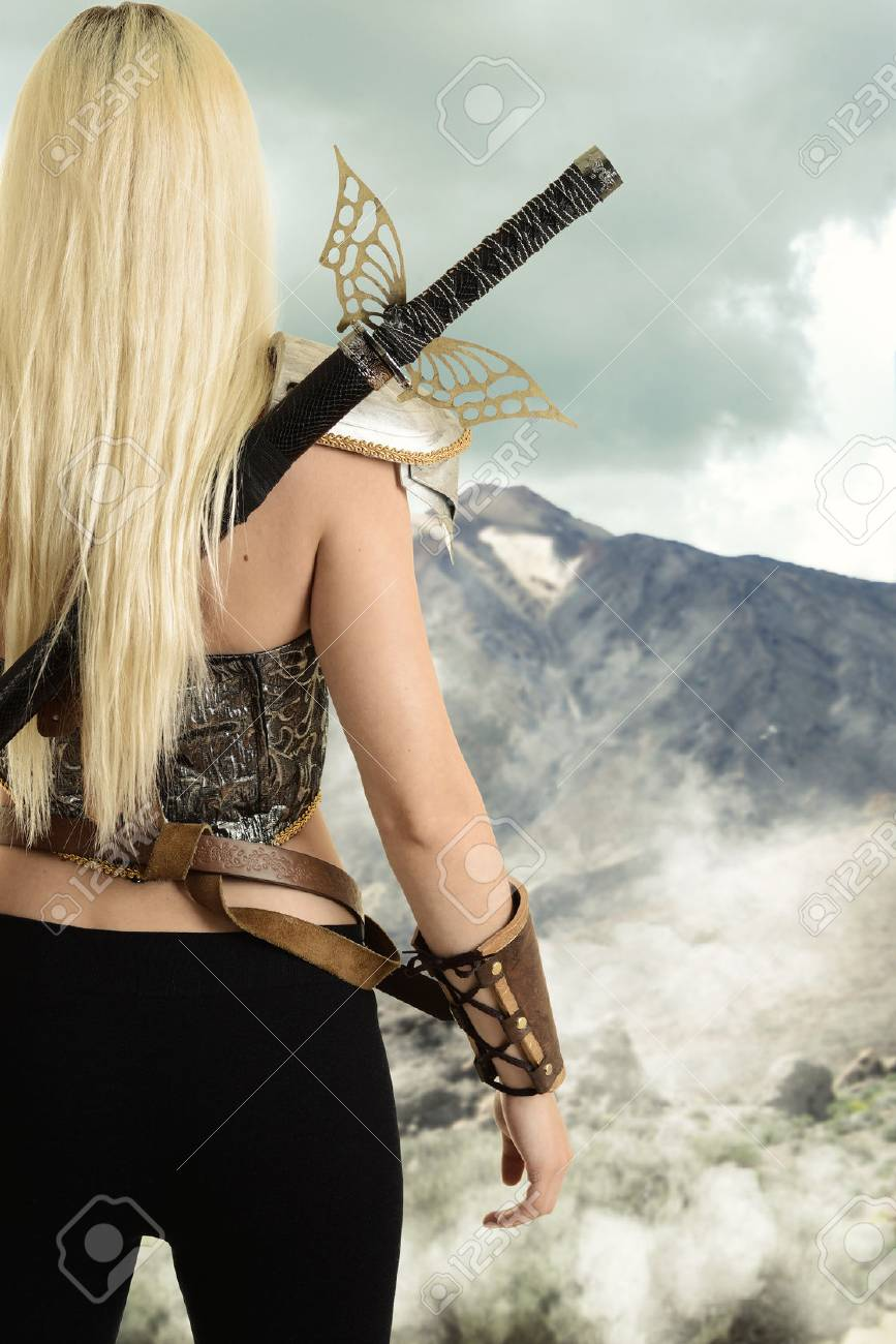 back of female warrior looking at mountain - 74472494