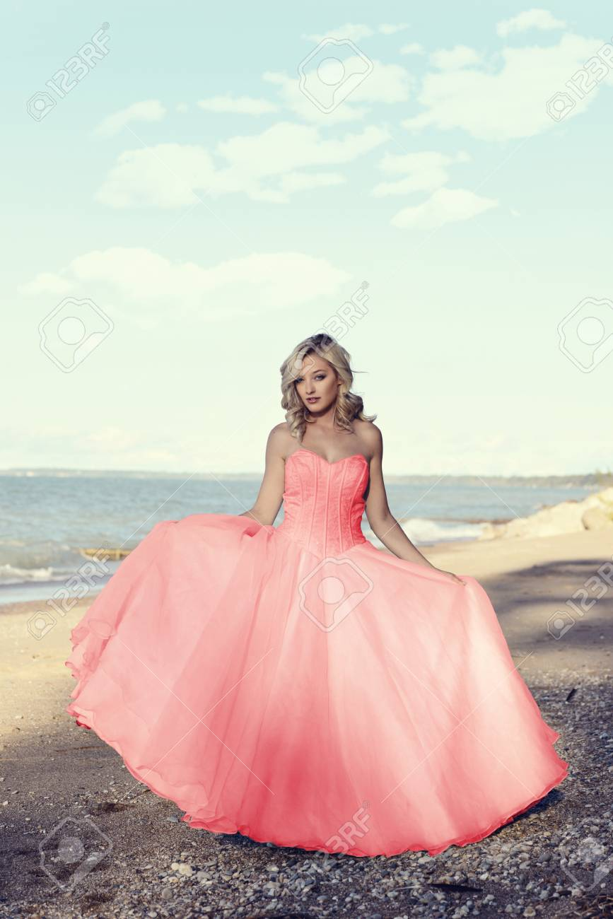 Young Blonde Woman At The Beach With Red Tulle Ball Dress Stock ...