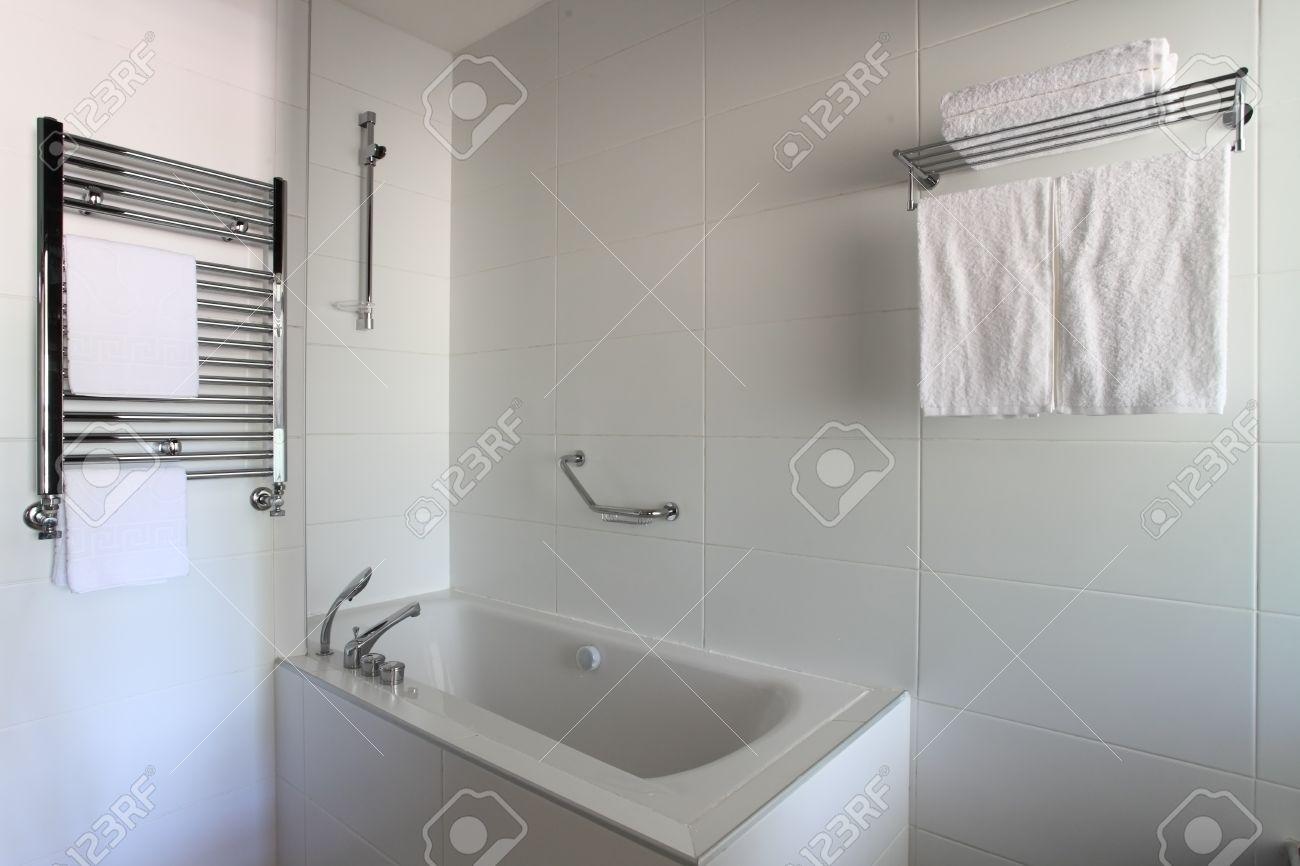 Bathtub, Heated Towel Rail And Shelf In Bathroom Stock Photo ...